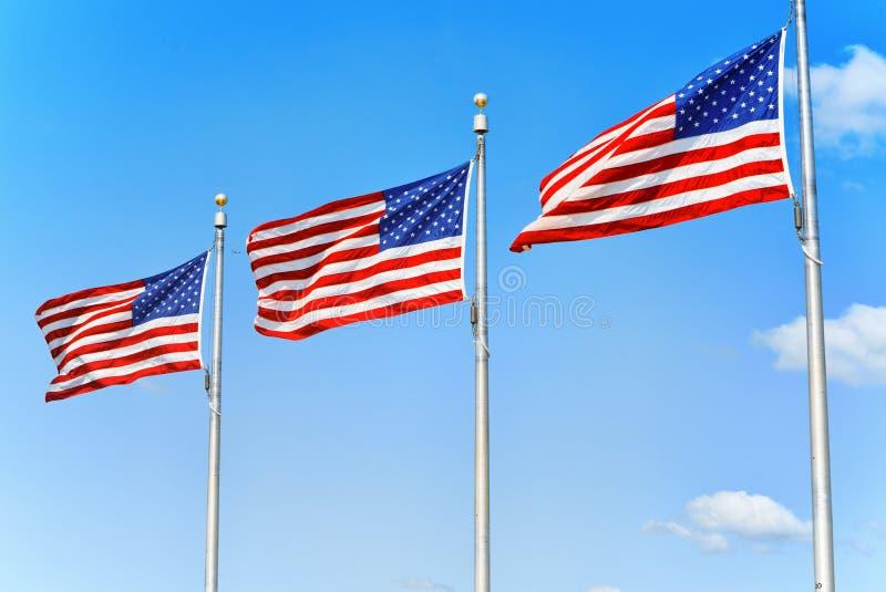 Αστέρι-ριγωτοί κυματισμοί αμερικανικών σημαιών υπερήφανα ενάντια στο μπλε SK στοκ φωτογραφίες