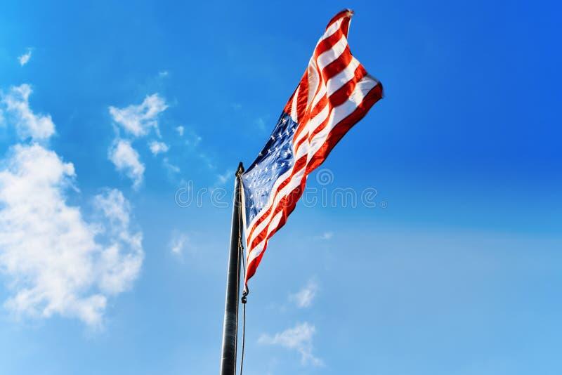 Αστέρι-ριγωτοί κυματισμοί αμερικανικών σημαιών υπερήφανα ενάντια στο μπλε ουρανό στοκ φωτογραφίες με δικαίωμα ελεύθερης χρήσης