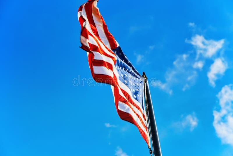 Αστέρι-ριγωτοί κυματισμοί αμερικανικών σημαιών υπερήφανα ενάντια στο μπλε ουρανό στοκ εικόνες με δικαίωμα ελεύθερης χρήσης