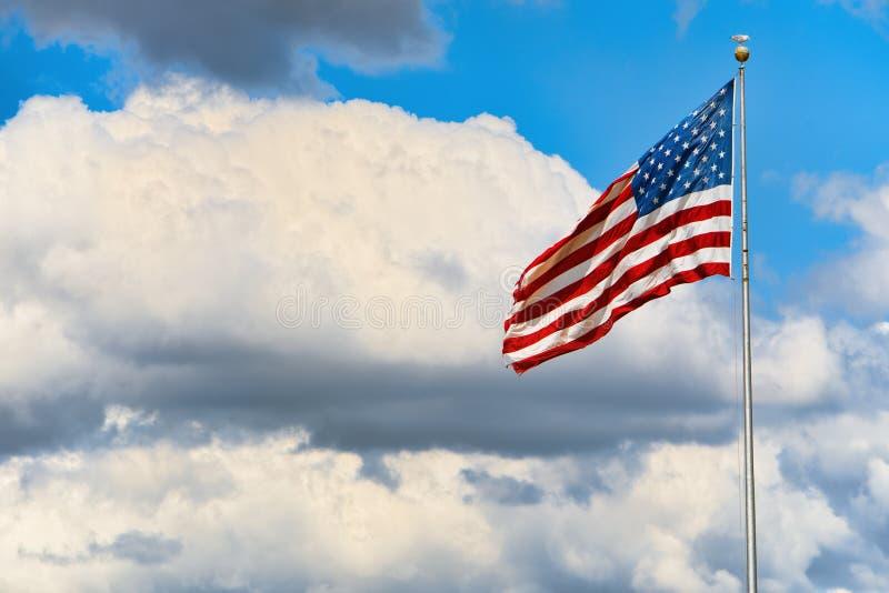 Αστέρι-ριγωτοί κυματισμοί αμερικανικών σημαιών υπερήφανα ενάντια στο μπλε ουρανό στοκ εικόνες