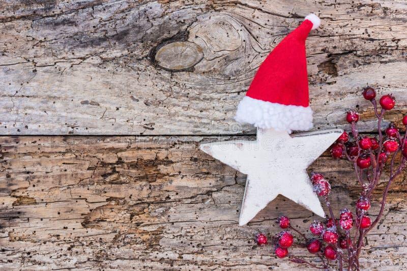 Αστέρι Χριστουγέννων με το καπέλο Άγιου Βασίλη κόκκινα μούρα στο ξύλινο υπόβαθρο στοκ φωτογραφία με δικαίωμα ελεύθερης χρήσης