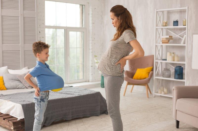 Αστεία έγκυα παίζοντας παιχνίδια μητέρων με λίγο γιο στοκ φωτογραφία με δικαίωμα ελεύθερης χρήσης
