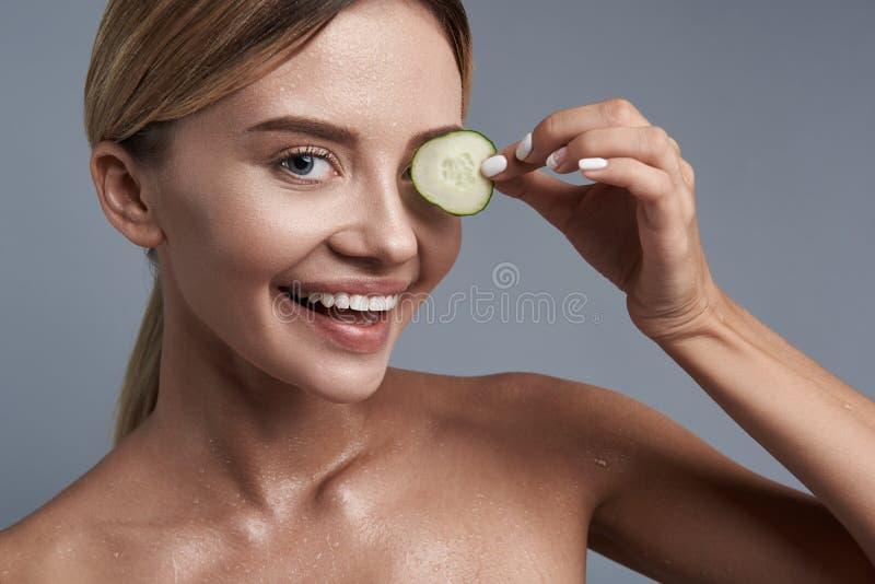 Αστεία γυναίκα που βάζει το κομμάτι του αγγουριού στο μάτι και το χαμόγελό της στοκ φωτογραφία