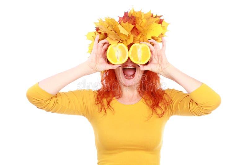 Αστεία γυναίκα φθινοπώρου με τα κίτρινα φύλλα στο κεφάλι και τα πορτοκάλια της στοκ εικόνα με δικαίωμα ελεύθερης χρήσης