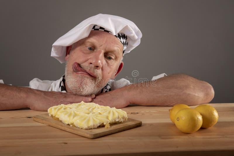 Αστεία εικόνα ενός ώριμου αρχιμάγειρα που θαυμάζει ένα κέικ λεμονιών στοκ φωτογραφία