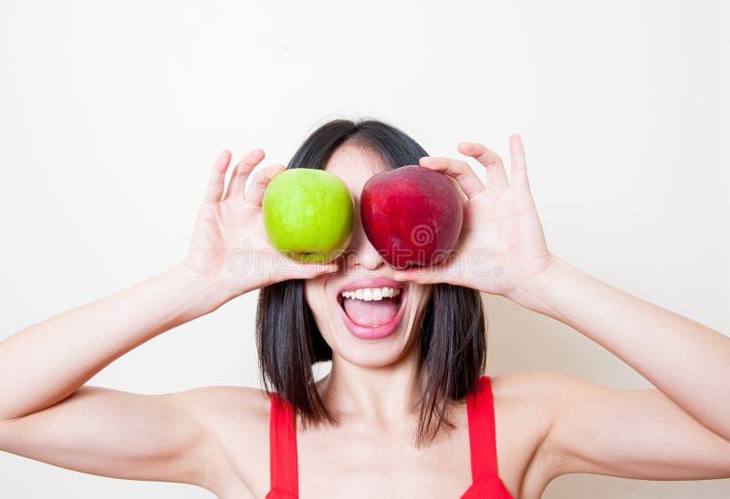 Αστεία νέα γυναίκα με τα κόκκινα και πράσινα μήλα πέρα από τα μάτια στοκ φωτογραφίες