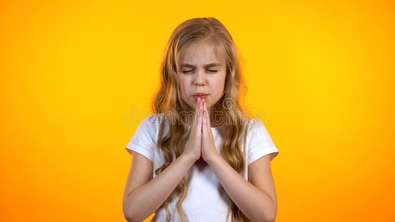 Αστεία ξανθή μαθήτρια που προσεύχεται πριν από το σχολικό διαγωνισμό, που ρωτά το έλεος, παιδαριώδης πεποίθηση στοκ φωτογραφία