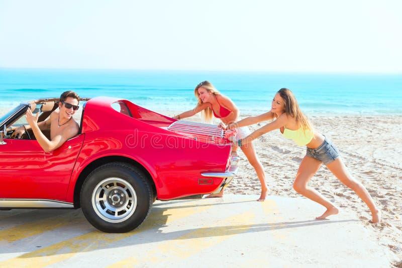 Αστεία οδήγηση τύπων χιούμορ κοριτσιών εφήβων ώθησης αυτοκινήτων στοκ εικόνες