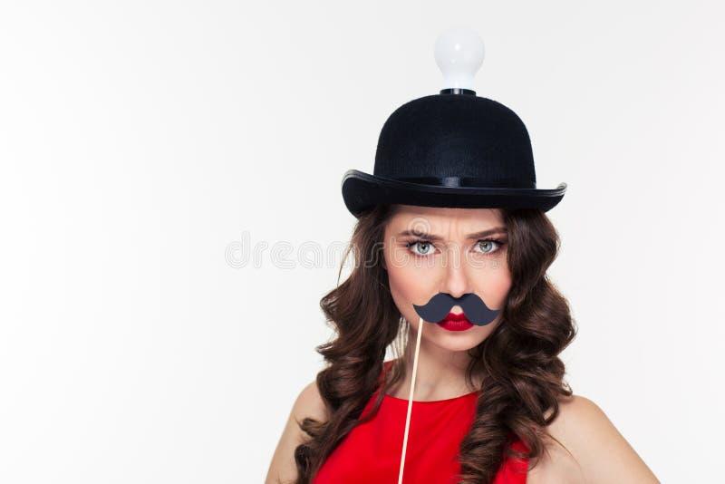 Αστεία σγουρή γυναίκα στο γελοίο μαύρο καπέλο με τη λάμπα φωτός στοκ εικόνα