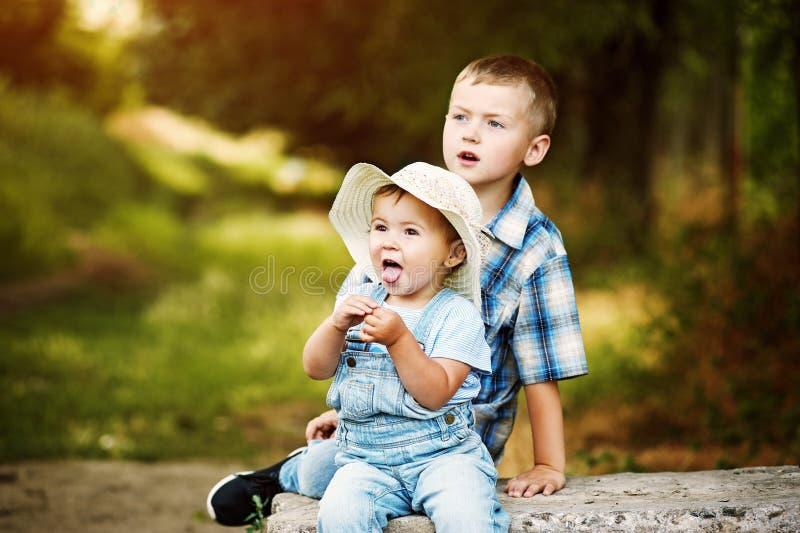 Αστεία συνεδρίαση μικρών κοριτσιών με τον αδελφό σας στο πάρκο στοκ εικόνες