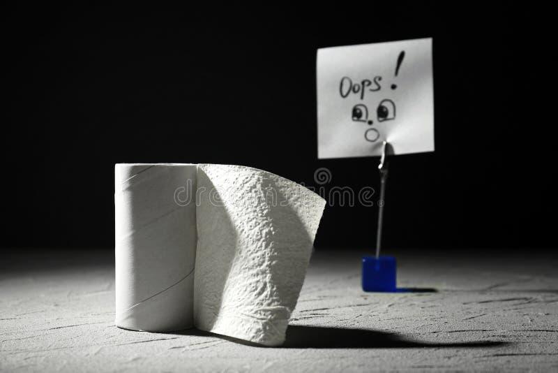 Αστεία σύνθεση με τον τελειωμένο ρόλο χαρτιού τουαλέτας στον γκρίζο πίνακα στοκ φωτογραφία με δικαίωμα ελεύθερης χρήσης