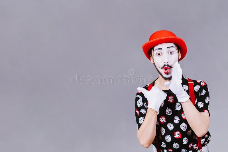 Αστεία τοποθέτηση mime κοντά σε ένα γκρίζο υπόβαθρο στοκ εικόνα