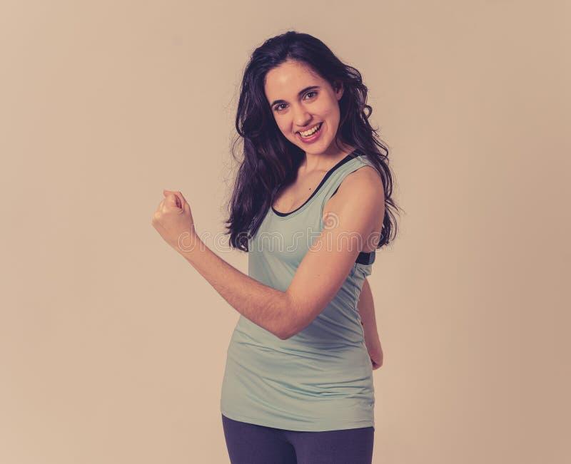 Αστεία φίλαθλη όμορφη γυναίκα brunette στα αθλητικά ενδύματα που τεντώνουν και που θέτουν ευτυχείς στοκ εικόνες