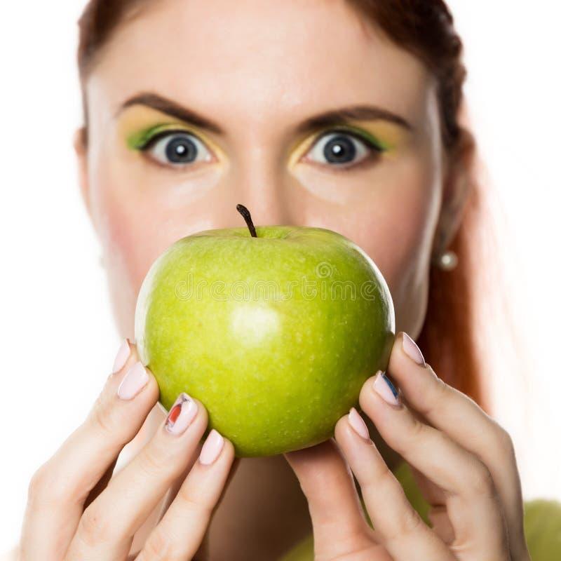 Αστεία redhead γυναίκα που κρατά το πράσινο μήλο υγιής τρόπος ζωής έννοιας στοκ φωτογραφία
