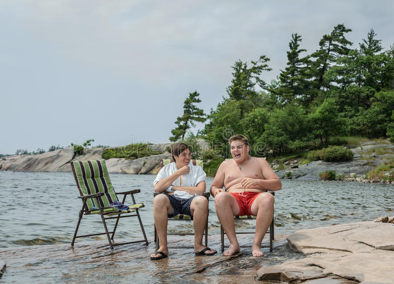 Αστείοι χαρούμενοι φίλοι που μιλούν τη χαλάρωση γέλιου στο πάρκο κοντά στη λίμνη στοκ εικόνα με δικαίωμα ελεύθερης χρήσης