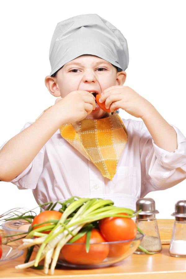 Αστείος λίγος μάγειρας που τρώει τις ντομάτες στοκ φωτογραφία