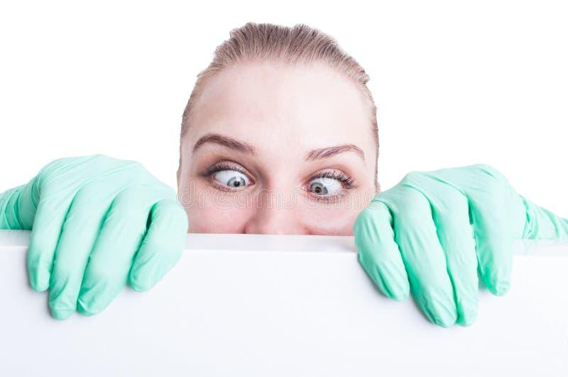 Αστείος γιατρός γυναικών που κρατά τα μάτια της διασχισμένα και την πράξη ανόητη στοκ φωτογραφία με δικαίωμα ελεύθερης χρήσης