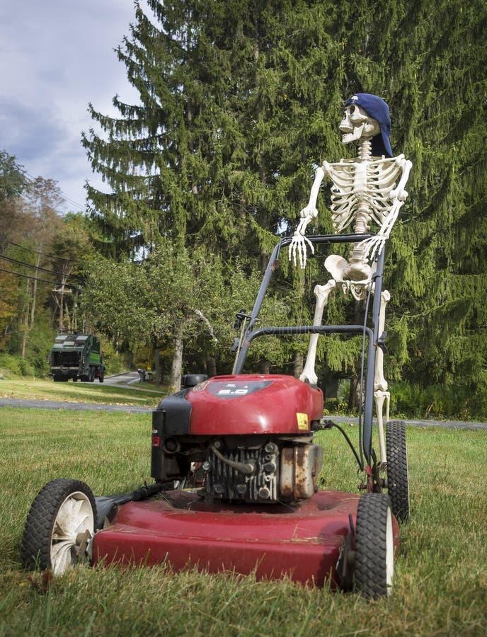Αστείος σκελετός που φορά ένα καπέλο του μπέιζμπολ που ωθεί έναν χορτοκόπτη στοκ φωτογραφία