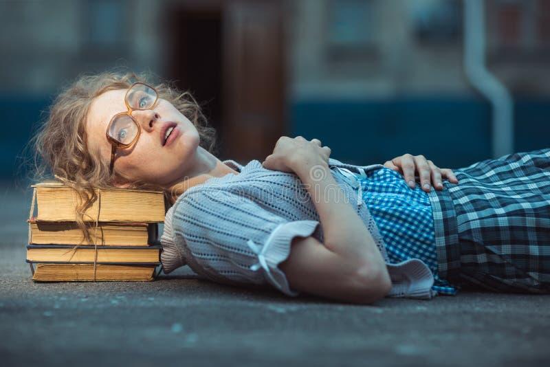 Αστείος τρελλός σπουδαστής κοριτσιών με τα γυαλιά που βρίσκονται σε έναν σωρό των βιβλίων στοκ φωτογραφία