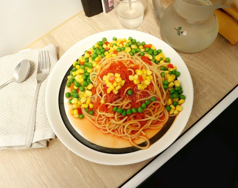 """Αστείου """"προσώπου τροφίμων φιαγμένου από μακαρόνια, σάλτσα ντοματών και μίγμα των λαχανικών στοκ φωτογραφία"""