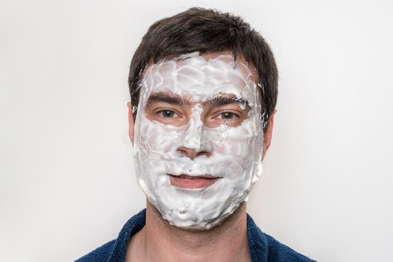 Αστείο άτομο με τη φυσική άσπρη μάσκα κρέμας στο πρόσωπό του στοκ φωτογραφίες