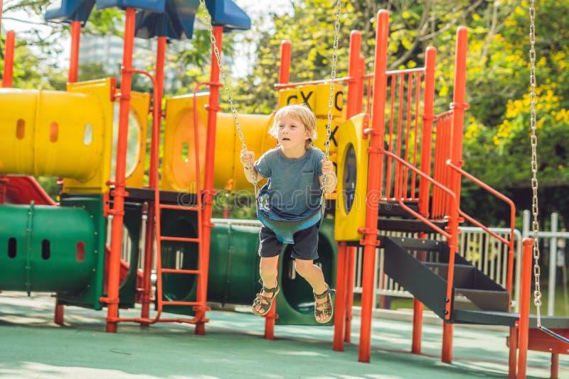 Αστείο αγόρι παιδιών που έχει τη διασκέδαση με την ταλάντευση αλυσίδων στην υπαίθρια παιδική χαρά παιδί που ταλαντεύεται τη θερμή στοκ φωτογραφία με δικαίωμα ελεύθερης χρήσης