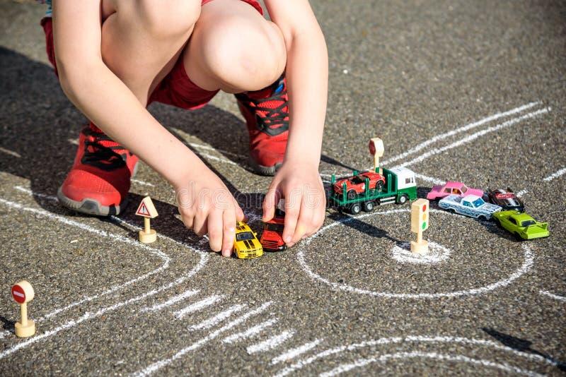 Αστείο αγόρι παιδιών που έχει τη διασκέδαση με το αυτοκίνητο κυκλοφορίας σχεδίων εικόνων με τις κιμωλίες Δημιουργικός ελεύθερος χ στοκ φωτογραφίες με δικαίωμα ελεύθερης χρήσης