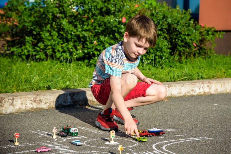 Αστείο αγόρι παιδιών που έχει τη διασκέδαση με το αυτοκίνητο κυκλοφορίας σχεδίων εικόνων με τις κιμωλίες Δημιουργικός ελεύθερος χ στοκ φωτογραφία με δικαίωμα ελεύθερης χρήσης