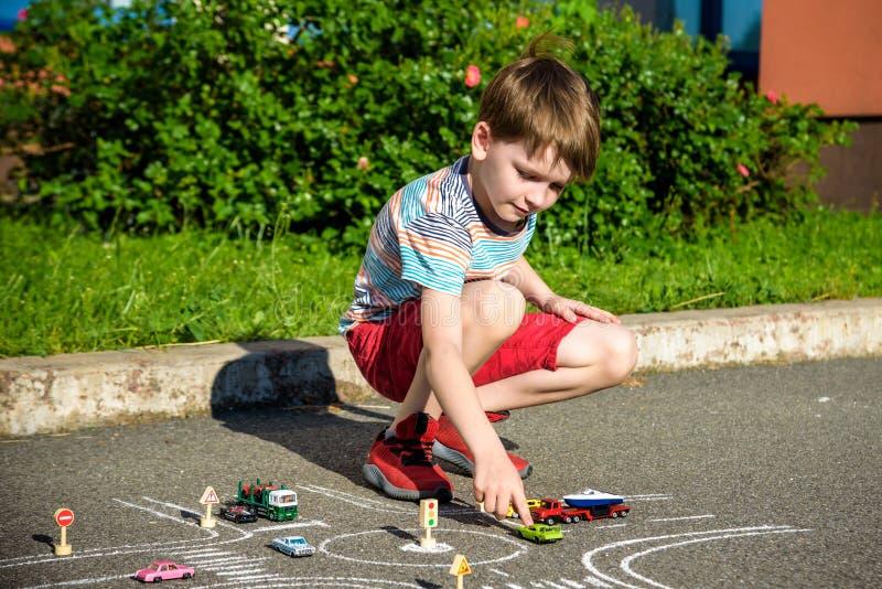 Αστείο αγόρι παιδιών που έχει τη διασκέδαση με το αυτοκίνητο κυκλοφορίας σχεδίων εικόνων με τις κιμωλίες Δημιουργικός ελεύθερος χ στοκ εικόνα με δικαίωμα ελεύθερης χρήσης
