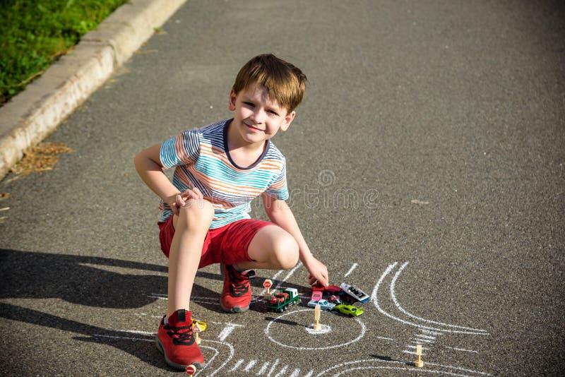 Αστείο αγόρι παιδιών που έχει τη διασκέδαση με το αυτοκίνητο κυκλοφορίας σχεδίων εικόνων με τις κιμωλίες Δημιουργικός ελεύθερος χ στοκ εικόνες