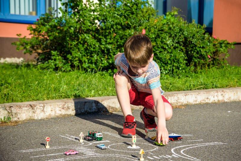 Αστείο αγόρι παιδιών που έχει τη διασκέδαση με το αυτοκίνητο κυκλοφορίας σχεδίων εικόνων με τις κιμωλίες Δημιουργικός ελεύθερος χ στοκ εικόνα