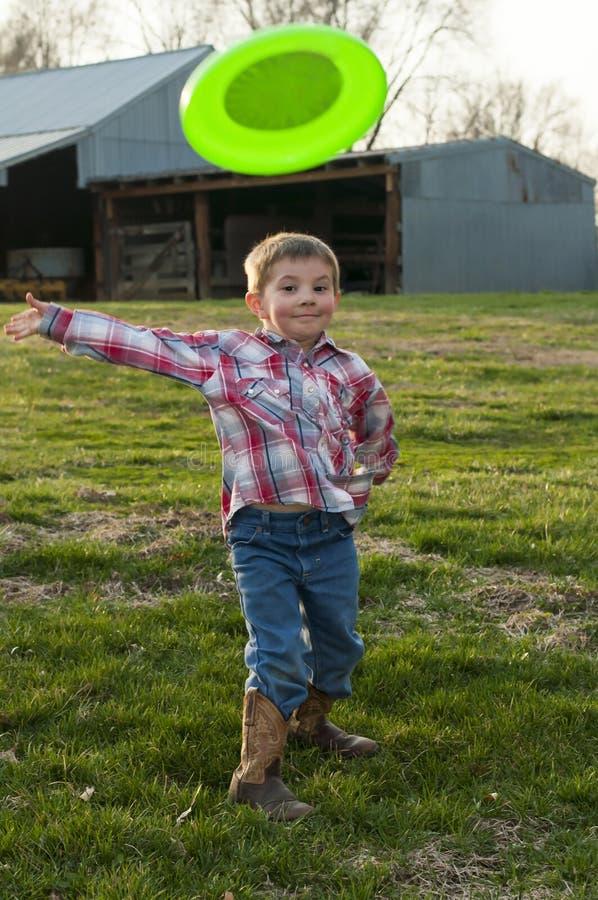 Αστείο αγόρι που ρίχνει το frisbee στοκ φωτογραφία