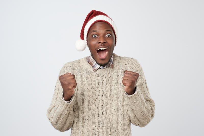 Αστείο αφρικανικό άτομο Χριστουγέννων στο κόκκινο καπέλο πέρα από το γκρίζο υπόβαθρο στοκ εικόνες