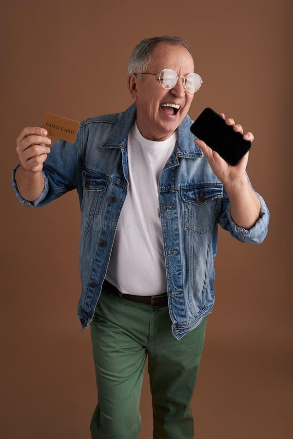 Αστείο ενήλικο άτομο που καυχάται το νέο smartphone και τη χρυσή κάρτα του στοκ φωτογραφία