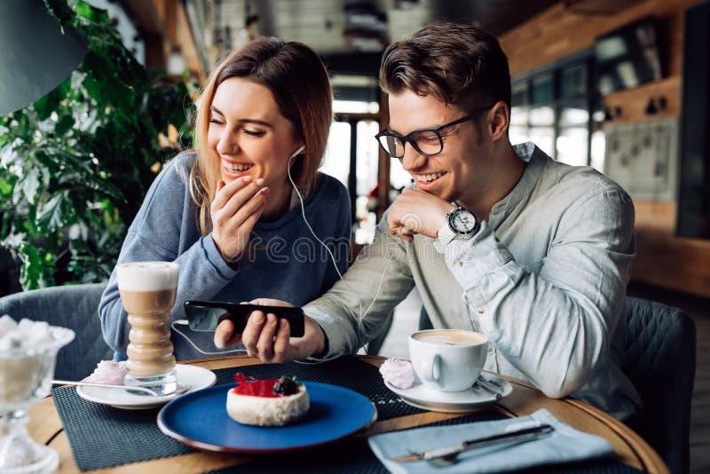 Αστείο ζεύγος που προσέχει έναν κινηματογράφο στο κινητό τηλέφωνο στηργμένος στον καφέ στοκ φωτογραφία