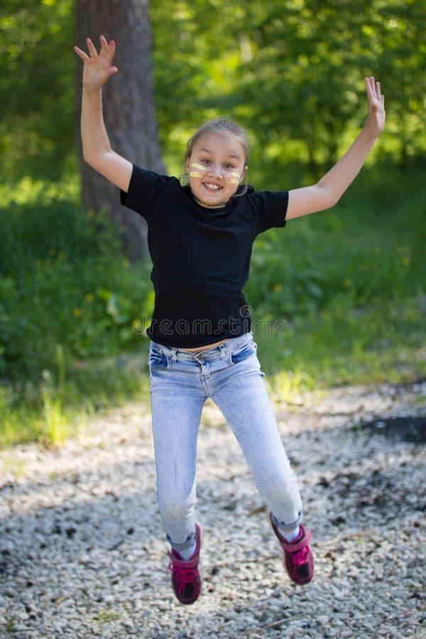 Αστείο κορίτσι εφήβων που πηδά και που έχει τη διασκέδαση στο πάρκο στην ηλιόλουστη ημέρα στοκ εικόνες