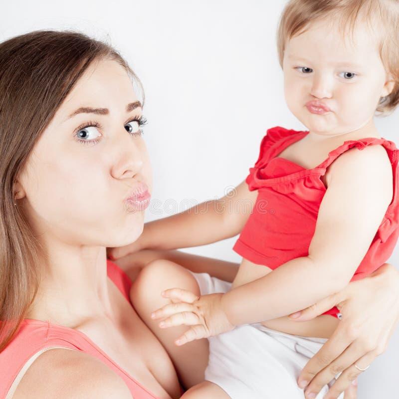 Αστείο κοριτσάκι κινηματογραφήσεων σε πρώτο πλάνο και η μητέρα της στο άσπρο υπόβαθρο στοκ εικόνες