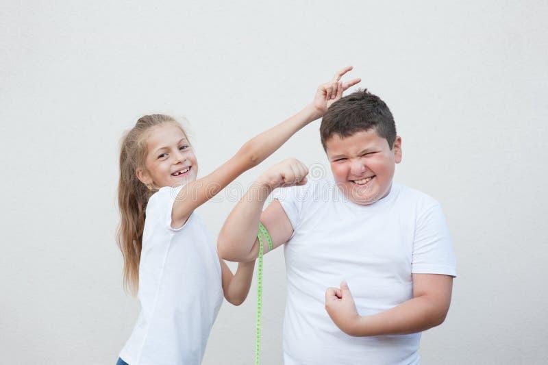 Αστείο λεπτό μικρό κορίτσι που μετρά μυ αγοριών χαμόγελου τον παχύ από την ταινία που γύρω στοκ εικόνες με δικαίωμα ελεύθερης χρήσης