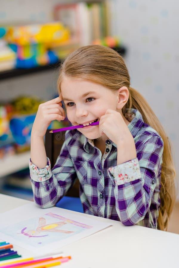 Αστείο μικρό κορίτσι με τη συνεδρίαση ξανθών μαλλιών στο πορφυρό μολύβι πινάκων και εκμετάλλευσης στο στόμα της στοκ φωτογραφία