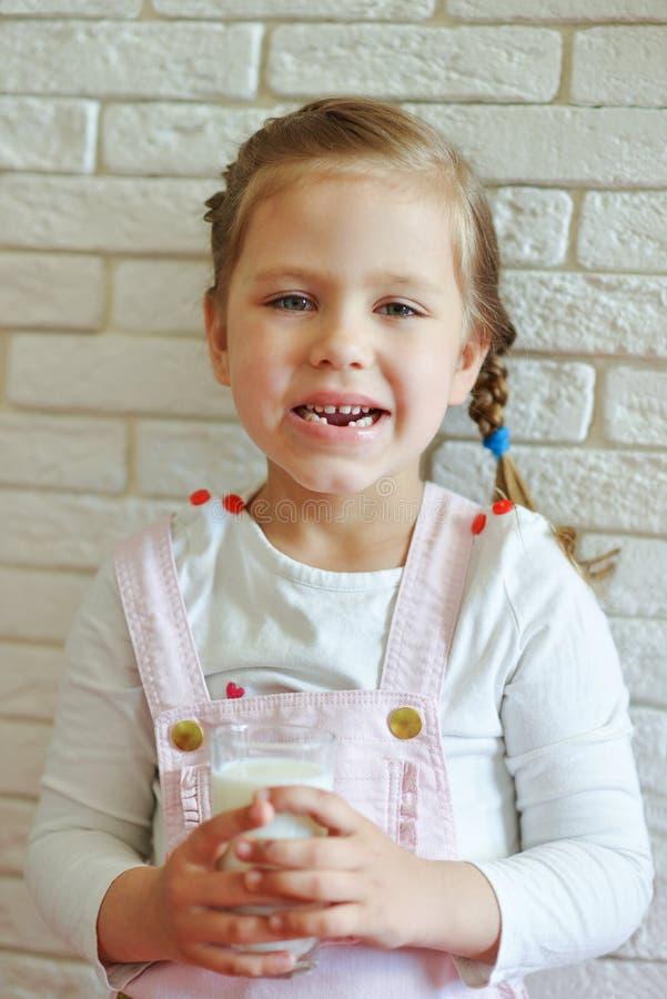 Αστείο μικρό κορίτσι με το ποτήρι του γάλακτος στοκ φωτογραφίες