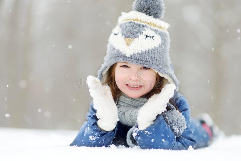 Αστείο μικρό κορίτσι που έχει τη διασκέδαση στο όμορφο χειμερινό πάρκο κατά τη διάρκεια των χιονοπτώσεων στοκ εικόνα