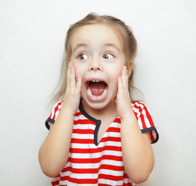Αστείο μικρό κορίτσι που αιφνιδιάζεται όπισθεν μεγάλη στοκ φωτογραφία
