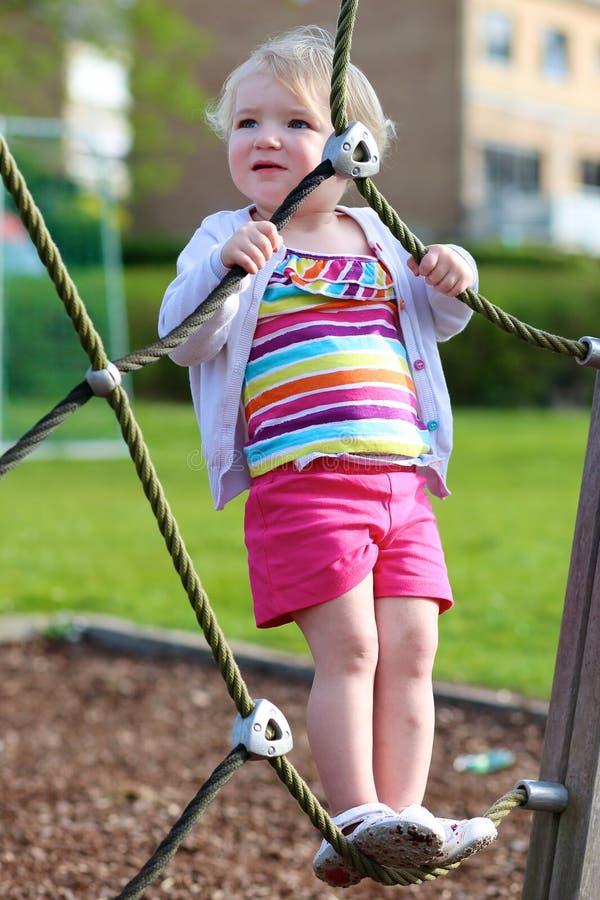 Αστείο μικρό κορίτσι που αναρριχείται στην παιδική χαρά στοκ εικόνα