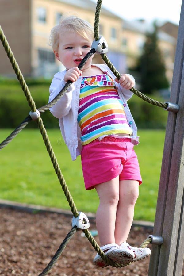 Αστείο μικρό κορίτσι που αναρριχείται στην παιδική χαρά στοκ εικόνες