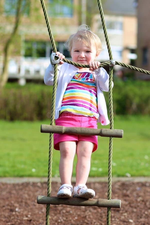 Αστείο μικρό κορίτσι που αναρριχείται στην παιδική χαρά στοκ φωτογραφία