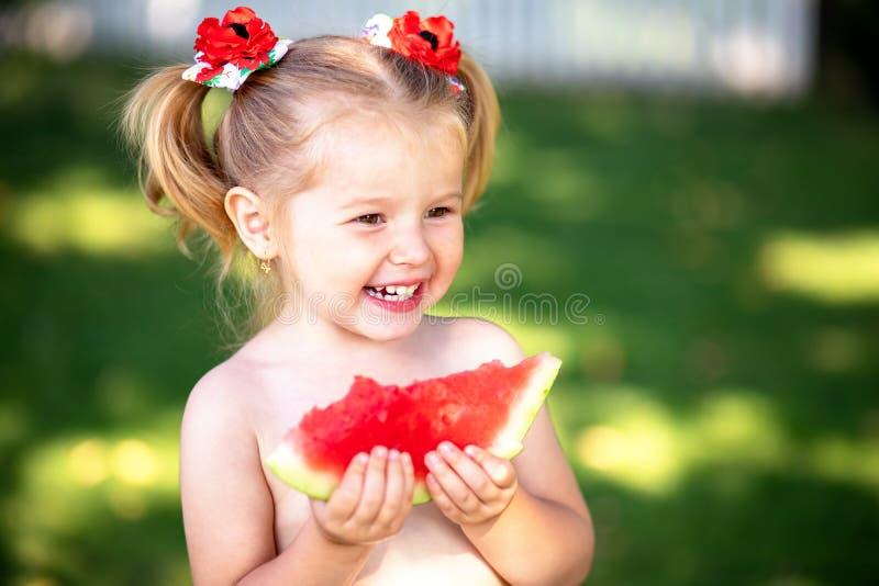 Αστείο μικρό κορίτσι που δαγκώνει μια φέτα του καρπουζιού υπαίθρια τη θερμή και ηλιόλουστη θερινή ημέρα Αντίγραφο, κενό διάστημα  στοκ φωτογραφία