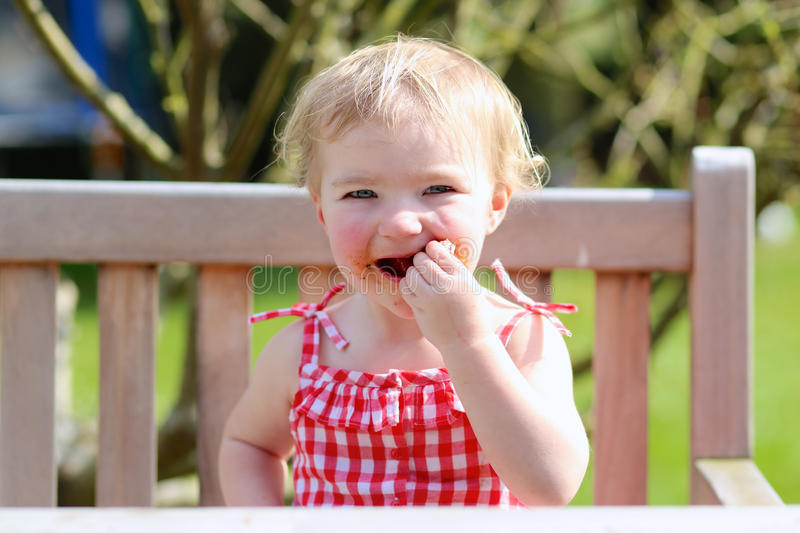 Αστείο μικρό κορίτσι που τρώει το ψημένο στη σχάρα κρέας από το κουτάλι στοκ εικόνες