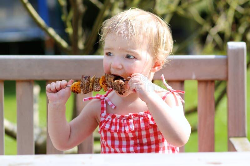 Αστείο μικρό κορίτσι που τρώει το ψημένο στη σχάρα κρέας από το κουτάλι στοκ φωτογραφία με δικαίωμα ελεύθερης χρήσης