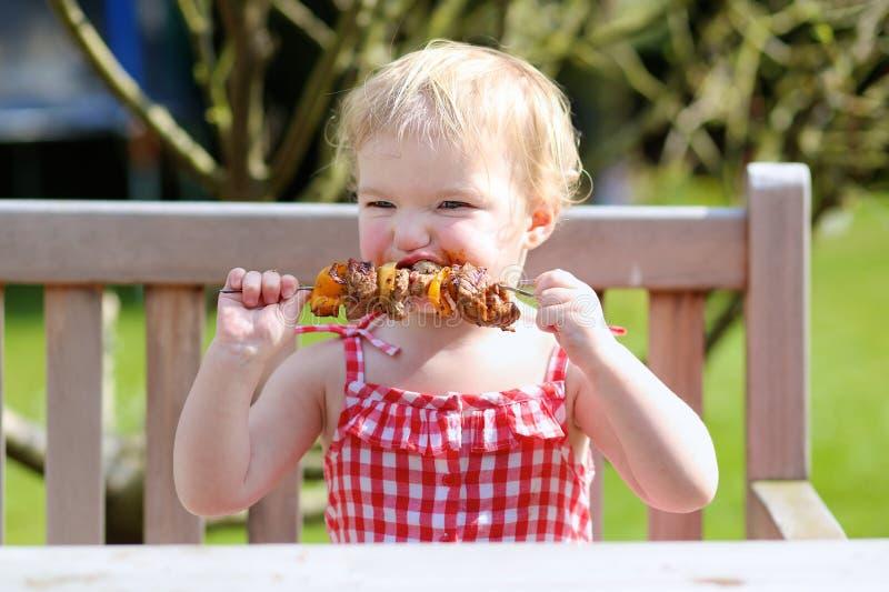 Αστείο μικρό κορίτσι που τρώει το ψημένο στη σχάρα κρέας από το κουτάλι στοκ φωτογραφίες με δικαίωμα ελεύθερης χρήσης