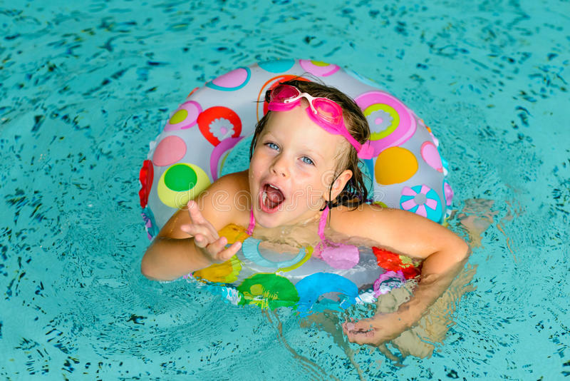 Αστείο μικρό κορίτσι στα ρόδινα προστατευτικά δίοπτρα στην πισίνα στοκ εικόνες